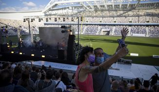 """Audience members wearing protective face masks take a selfie during a performance of Israeli musician Ivri Lider, where all guests were required to show """"green passport"""" proof of receiving a COVID-19 vaccination or full recovery from the virus at a soccer stadium in Tel Aviv, Friday, March. 5, 2021. (AP Photo/Oded Balilty)"""