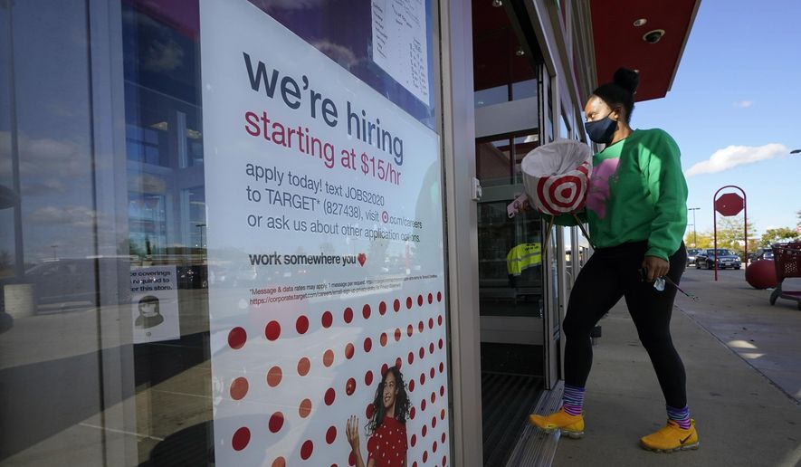 In this Sept. 30, 2020, file photo, a passerby walks past a hiring sign while entering a Target store in Westwood, Mass. The number of Americans applying for unemployment benefits edged higher last week to 745,000, a sign that many employers continue to cut jobs despite a drop in confirmed viral infections and evidence that the overall economy is improving. (AP Photo/Steven Senne, File)
