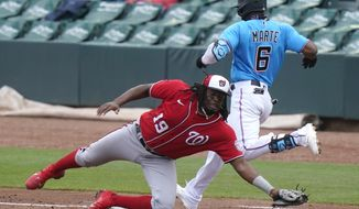 Miami Marlins' Starling Marte (6) beats the throw to Washington Nationals first baseman Josh Bell (19) for a single during the third inning of a spring training baseball game, Saturday, March 6, 2021, in Jupiter, Fla. (AP Photo/Lynne Sladky)