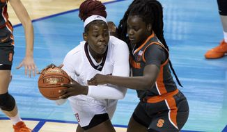 Louisville's Olivia Cochran, left, handles the ball in the post as Syracuse's Maeva Djaldi-Tabdi, right, defends during the first half of an NCAA college basketball game in the semifinals of Atlantic Coast Conference tournament in Greensboro, N.C., Saturday, March 6, 2021. (AP Photo/Ben McKeown)