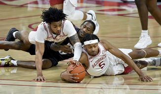 Arkansas guard Desi Sills left,, Texas A&M guard Quenton Jackson, center, and Arkansas guard Moses Moody (5) fight for the ball during the first half of an NCAA college basketball game in Fayetteville, Ark., Saturday, March 6, 2021. (AP Photo/Michael Woods)