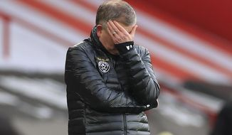 Sheffield United's manager Chris Wilder covers his face during an English Premier League soccer match between Sheffield United and Southampton at the Bramall Lane stadium in Sheffield, England, Saturday March 6, 2021. (Mike Egerton/Pool via AP)