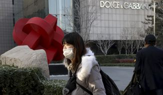 FILE - In this Nov. 25, 2018 file photo, a woman walks past a Dolce&Gabbana retail outlet in Beijing, China. The Milan fashion house Dolce&Gabbana filed a multi-million-dollar defamation suit in an Italian court against U.S. fashion bloggers who reposted anti-Asian comments attributed to one of the designers that led to a boycott by Asian consumers. The suit was filed in Milan civil court in 2019, but only became public this week, Thursday, March 4, 2021, when the bloggers posted about it on their Instagram profile, Diet Prada.  (AP Photo/Ng Han Guan, file)