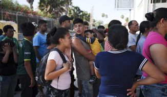 FILE - In this July 31, 2019 file photo, migrants line up in Matamoros, Mexico, for a meal donated by volunteers from the U.S., at the foot of the Puerta Mexico bridge that crosses to Brownsville, Texas. Some asylum seekers were told by officials Friday, March 5, 2021, that the U.S. government may reopen their cases and they would eventually be able to enter the U.S. to wait out the asylum process. (AP Photo/Emilio Espejel, File)