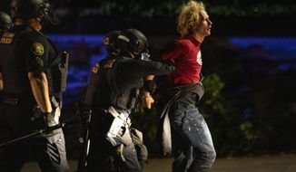 FILE - In this Aug. 30 2020 file photo police make arrests on the scene of protests at a Portland police precinct on in Portland, Ore. Amid protests following the police killing of George Floyd last year Portland dissolved a special police unit designed to focus on gun violence. Critics say the squad unfairly targeted Black people, but gun violence and homicides have since spiked in Oregon's largest city, and some say disbanding the 35-officer unit was a mistake. (AP Photo/Paula Bronstein,File)