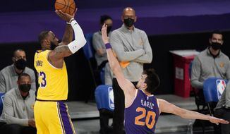 Los Angeles Lakers forward LeBron James, left, shoots as Phoenix Suns forward Dario Saric defends during the first half of an NBA basketball game Tuesday, March 2, 2021, in Los Angeles. (AP Photo/Mark J. Terrill)