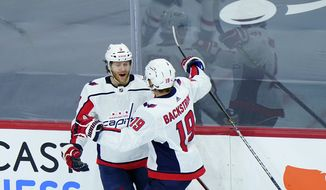 Washington Capitals' Nick Jensen (3) and Nicklas Backstrom (19) celebrate after Jensen's goal during the third period of an NHL hockey game against the Philadelphia Flyers, Sunday, March 7, 2021, in Philadelphia. (AP Photo/Matt Slocum)
