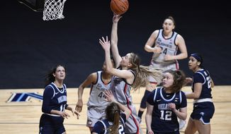 Connecticut's Paige Bueckers, center, shoots as Villanova's Bella Runyan (32) defends during the first half of an NCAA college basketball game in the Big East tournament semifinals at Mohegan Sun Arena, Sunday, March 7, 2021, in Uncasville, Conn. (AP Photo/Jessica Hill)