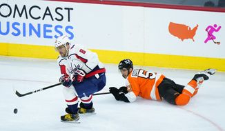 Washington Capitals' Alex Ovechkin (8) keeps the puck away from Philadelphia Flyers' Shayne Gostisbehere (53) during the third period of an NHL hockey game, Sunday, March 7, 2021, in Philadelphia. (AP Photo/Matt Slocum)