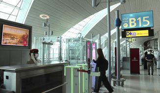 A woman enters the face and iris-recognition gate to board a plane, during a media tour at Dubai Airport, in the United Arab Emirates, Sunday, March 7, 2021. Dubai's airport, the world's busiest for international travel, has introduced an iris-scanner that verifies one's identity and eliminates the need for any human interaction when leaving the country. It's the latest artificial intelligence program the UAE has launched amid the surging coronavirus pandemic. (AP Photo/Kamran Jebreili)