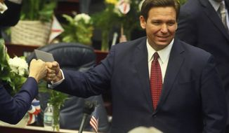 FILE - In this Tuesday, March 1, 2021 file photo, Florida Gov. Ron DeSantis fist bumps with legislators as he enters the House of Representatives prior to his State of the State address at the Capitol in Tallahassee, Fla. Democrats hope to make deeper strides in changing their fortunes in a state that has become friendlier place for Republicans. The state's only Democrat in statewide office, Agriculture Commissioner Nikki Fried is contemplating a challenge to Republican Gov. DeSantis.  (AP Photo/Phil Sears, File)