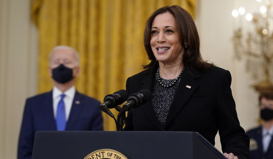 Vice President Kamala Harris speaks as President Joe Biden listens during an event to mark International Women's Day, Monday, March 8, 2021, in the East Room of the White House in Washington. (AP Photo/Patrick Semansky)