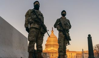 National Guard troops stand their posts around the Capitol at sunrise in Washington, Monday, March 8, 2021. (AP Photo/Carolyn Kaster) **FIILE**