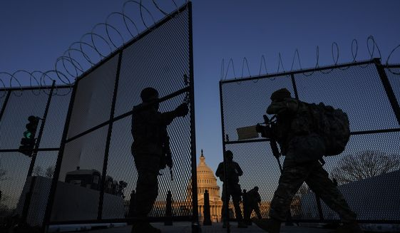 National Guard open a gate in the razor wire topped perimeter fence around the Capitol to allow others in at sunrise in Washington, Monday, March 8, 2021. (AP Photo/Carolyn Kaster)