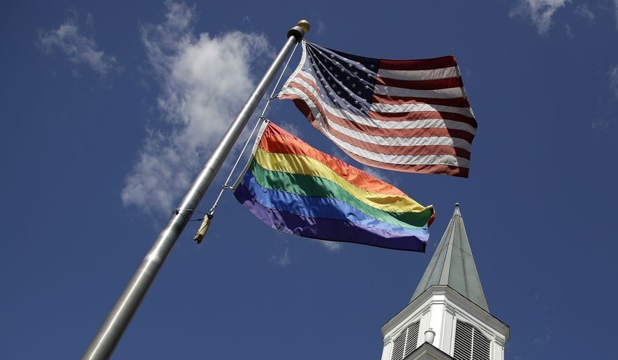 In this Friday, April 19, 2019 file photo, a gay pride rainbow flag flies with the U.S. flag in front of the Asbury United Methodist Church in Prairie Village, Kan.  (AP Photo/Charlie Riedel)  **FILE**