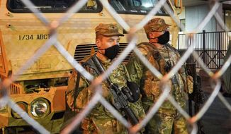 National Guard troops watch the pedestrian entrance Monday, March 8, 2021, at the Hennepin County Courthouse in Minneapolis, Minn., the site of the trial of former Minneapolis police officer Derek Chauvin in the death of George Floyd. (Glen Stubbe/Star Tribune via AP)
