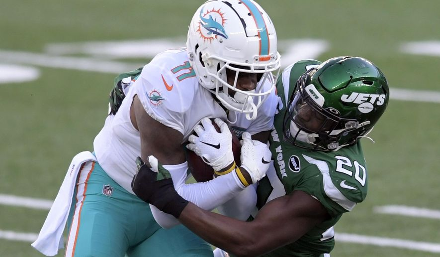 FILE - In this Nov. 29, 2020, file photo, New York Jets free safety Marcus Maye (20) tackles Miami Dolphins wide receiver DeVante Parker (11) during the first half of an NFL football game in East Rutherford, N.J. A person with direct knowledge of the move says the Jets placed the franchise tag on Maye, a steady playmaker and leader with whom the team hopes to work out a long-term deal. (AP Photo/Bill Kostroun, File)