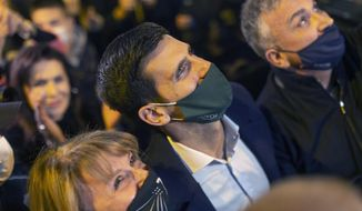 Novak Djokovic, center, Serbian tennis player, is surrounded by fans as he arrives at a restaurant, Belgrade, Serbia, Monday, March 8, 2021. Djokovic surpassed Roger Federer for the most weeks at No. 1 in the ATP rankings on Monday. Djokovic is in his 311th week in the top spot. (AP Photo/Marko Drobnjakovic)