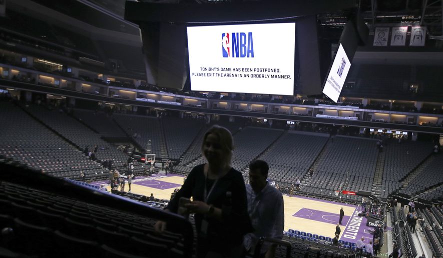 In this March 11, 2020, file photo, fans leave the Golden 1 Center after the NBA basketball game between the New Orleans Pelicans and Sacramento Kings  in Sacramento, Calif., was postponed at the last minute due to the coronavirus. A year after the worldwide coronavirus pandemic stopped all the games in their tracks, the aftershocks are still being felt across every sector.  (AP Photo/Rich Pedroncelli, File) **FILE**