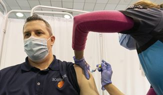 Greg Brennan, a teacher and basketball coach at Southside High School, is vaccinated by nurse Abigail Fromm, at a clinic operated by Mount Sinai South Nassau, Friday, March 5, 2021, in Rockville Centre, N.Y. Brennan received the first of two Moderna COVID-19 vaccines. (AP Photo/Mark Lennihan)