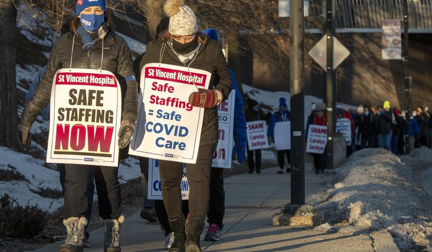 Striking nurses walk the picket line outside Saint Vincent Hospital in Worcester, Mass., as the sun rises on the first day of a strike Monday, March 8, 2021. Hundreds of nurses at the central Massachusetts hospital walked off the job on Monday morning after failing to reach an agreement with management over staffing levels.  (Rick Cinclair/Worcester Telegram & Gazette via AP)