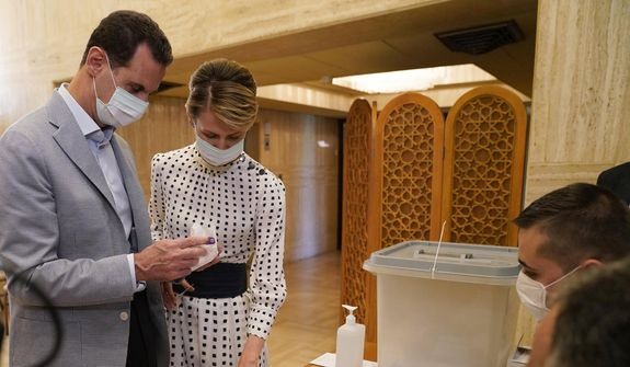 This file photo released on July 19, 2020, on the official Facebook page of the Syrian Presidency, shows Syrian President Bashar Assad, left, and his wife Asma voting at a polling station in the parliamentary elections, in Damascus, Syria. (Syrian Presidency via AP, File)