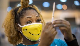 Medical Assistant Keona Shepard holds up the Johnson & Johnson COVID-19 vaccine as she prepares to administer it at the New Orleans Ernest N. Morial Convention Center during the mass coronavirus vaccination on Thursday, March 4, 2021 in New Orleans. (Chris Granger /The Advocate via AP)