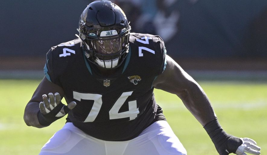 """FILE - Jacksonville Jaguars offensive tackle Cam Robinson (74) sets up to block during the first half of an NFL football game against the Chicago Bears in Jacksonville, Fla., in this Sunday, Dec. 27, 2020, file photo. The Jaguars are planning to use the franchise tag on left tackle Cam Robinson, preventing him from hitting the free-agent market and making him the blindside protector for presumptive No. 1 draft pick Trevor Lawrence. Coach Urban Meyer said Tuesday, March 9, 2021, that """"we are headed in that direction."""" (AP Photo/Phelan M. Ebenhack, File)"""