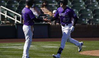 Colorado Rockies' Trevor Story (27) high-fives Dom Nunez (3) after scoring a three run homer during the third inning of a spring training baseball game against the Milwaukee Brewers Friday, March 5, 2021, in Scottsdale, Ariz. (AP Photo/Ashley Landis)