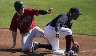Arizona Diamondbacks' Josh VanMeter (19) steals third base as Cleveland Indians third baseman Jose Ramirez, right, is unable to control the throw during the third inning of a spring training baseball game Wednesday, March 3, 2021, in Goodyear, Ariz. (AP Photo/Ross D. Franklin)