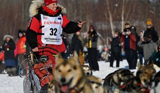 Aliy Zirkle, of Two Rivers, greets fans as she passes by at the Iditarod Sled Dog Race start at Deshka Landing in Willow, Alaska, Sunday, March 7, 2021. (Marc Lester/Anchorage Daily News via AP)