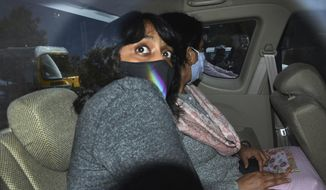 FILE - In this Feb. 22, 2021, file photo, climate activist Disha Ravi, 22, travels in a car as she is taken to a court in New Delhi, India. To her friends, Ravi, was most concerned about her future in a world where temperatures are rising. But her life changed last month as she became a household name in the country, dominating news coverage after police charged her with sedition, a colonial-era law which carries a sentence up to life. Her alleged crime: sharing an online document to help amplify months-long farmer protests in India on Twitter. She was released after 10 days in custody. (AP Photo/Dinesh Joshi, File)