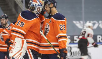 Edmonton Oilers goalie Mikko Koskinen (19) and Darnell Nurse (25) celebrate a win over the Ottawa Senators during third-period NHL hockey game action in Edmonton, Alberta, Monday, March 8, 2021. (Jason Franson/The Canadian Press via AP)
