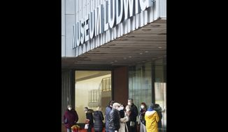 Visitors wait for the opening of the Museum Ludwig in Cologne, Germany, Tuesday, March 9, 2021. More than 100 Andy Warhol originals have been hanging on the walls of Cologne's Museum Ludwig since mid-December with nobody to view them after coronavirus restrictions shut down galleries across the country. That changed on Tuesday as the doors were opened to limited numbers of guests, after authorities eased restrictions to allow some museums, galleries and certain other cultural venues to begin receiving visitors again. (Oliver Berg/dpa via AP)