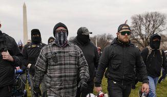 In this Jan. 6, 2021, photo, Proud Boy members Joseph Biggs, left, and Ethan Nordean, right with megaphone, walk toward the U.S. Capitol in Washington, in support of President Donald Trump. The Proud Boys and Oath Keepers make up a fraction of the more than 300 Trump supporters charged so far in the siege that led to Trump's second impeachment and resulted in the deaths of five people, including a police officer. But several of their leaders, members and associates have become the central targets of the Justice Departments sprawling investigation. (AP Photo/Carolyn Kaster)