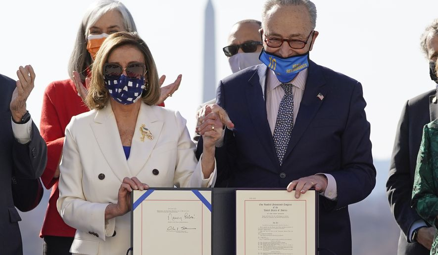 House Speaker Nancy Pelosi of Calif., and Senate Majority Leader Chuck Schumer of N.Y., pose after signing the $1.9 trillion COVID-19 relief bill during an enrollment ceremony on Capitol Hill, Wednesday, March 10, 2021, in Washington. (AP Photo/Alex Brandon)