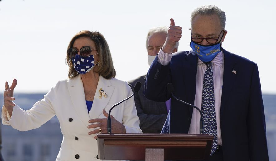 House Speaker Nancy Pelosi of Calif., and Senate Majority Leader Chuck Schumer of N.Y., gesture during an enrollment ceremony for the $1.9 trillion COVID-19 relief bill, on Capitol Hill, Wednesday, March 10, 2021, in Washington. (AP Photo/Alex Brandon)