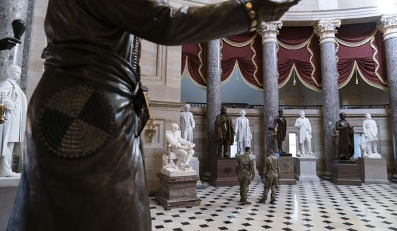 Two U.S. Army National Guard soldiers walk in Statuary Hall on Wednesday, March 10, 2021, in Washington, in this file photo. (AP Photo/Alex Brandon)  **FILE**
