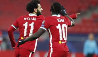 Liverpool's Mohamed Salah, left, celebrates after scoring his side's opening goal during the Champions League round of 16 second leg soccer match between Liverpool and RB Leipzig at the Puskas Arena stadium in Budapest, Hungary, Wednesday, March 10, 2021. (AP Photo/Laszlo Balogh)