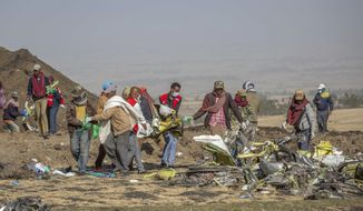 FILE - In this March 11, 2019 file photo, rescuers work at the scene of an Ethiopian Airlines flight crash near Bishoftu, or Debre Zeit, south of Addis Ababa, Ethiopia.  Relatives of some of the passengers who died in the crash will mark the two-year anniversary of the disaster on Wednesday, March 10, 2021, by seeking a reversal of government orders that let Boeing 737 Max jets fly again.  (AP Photo/Mulugeta Ayene, File)