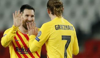 Barcelona's Lionel Messi, left, celebrates after scoring his side's opening goal with Barcelona's Antoine Griezmann during the Champions League, round of 16, second leg soccer match between Paris Saint-Germain and FC Barcelona at the Parc des Princes stadium in Paris, Wednesday, March 10, 2021. (AP Photo/Christophe Ena)