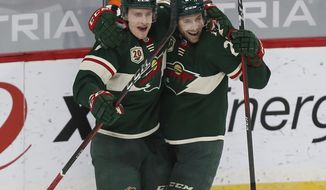 Minnesota Wild's Nico Sturm, left, celebrates with Carson Soucy (21) after Soucy scored a goal during the third period of the team's NHL hockey game against the Vegas Golden Knights, Wednesday, March 10, 2021, in St. Paul, Minn. The Wild won 4-3. (AP Photo/Stacy Bengs)