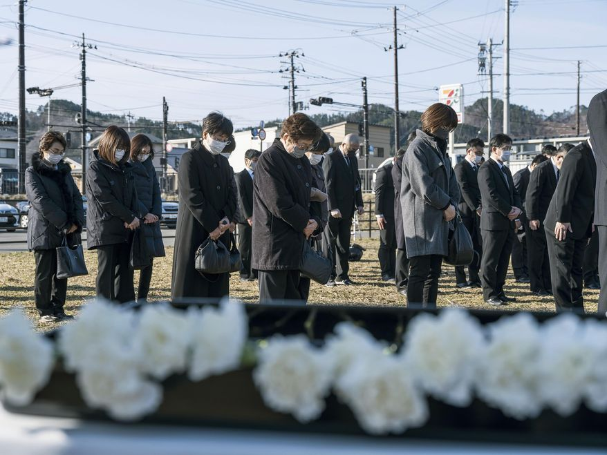 People offer a silent prayer for victims of the 2011 massive earthquake and tsunami, on the site of former town office in Otsuchi, Iwate prefecture, Japan Thursday, March 11, 2021. Thursday marks the 10th anniversary of the massive earthquake, tsunami and nuclear disaster that struck Japan's northeastern coast. (Koki Sengoku/Kyodo News via AP)