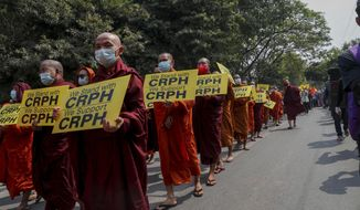 """Buddhist monks, supporters of anti-coup protesters display placards during a march through the streets of Mandalay, Myanmar, Wednesday, March 10, 2021. CRPH stands for Committee Representing elected members of the Union Parliament from the National League for Democracy Party"""". (AP Photo)"""