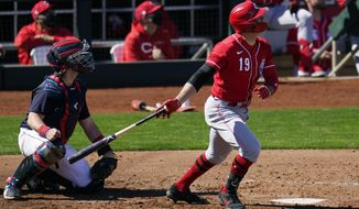 Cincinnati Reds' Joey Votto (19) watches his run-scoring single hit to left field as Cleveland Indians catcher Austin Hedges, left, looks on during the third inning of a spring training baseball game Sunday, Feb. 28, 2021, in Goodyear, Ariz. (AP Photo/Ross D. Franklin)