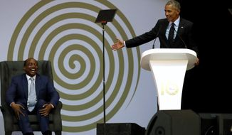 FILE - in this file photo dated Tuesday, July 17, 2018, former U.S. President Barack Obama, right, delivers his speech, as Patrice Motsepe, left, looks on at the 16th Annual Nelson Mandela Lecture at the Wanderers Stadium in Johannesburg, South Africa.  The election to lead African soccer is seeming to be dominated by FIFA president Gianni Infantino, who supports South African billionaire Patrice Motsepe to win the top job in a ballot next week. (AP Photo/Themba Hadebe, FILE)