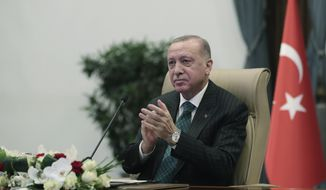"""Turkey's Recep Tayyip Erdogan applauds as he listens to Russia's President Vladimir Putin during a ceremony as they have remotely inaugurated the construction of a third nuclear reactor of Akkuyu power plant in Mersin province on the Mediterranean coast, in Ankara, Turkey, Wednesday, March 10, 2021. Erdogan called it a """"symbol of Turkish-Russian cooperation."""" (Turkish Presidency via AP, Pool)"""