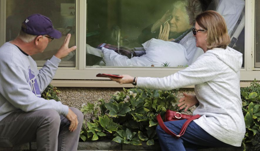 FILE - In this March 11, 2020, file photo Judie Shape, center, who has tested positive for the coronavirus, blows a kiss to her son-in-law, Michael Spencer, left, as Shape's daughter, Lori Spencer, right, looks on, as they visit on the phone and look at each other through a window at the Life Care Center in Kirkland, Wash., near Seattle. Nursing home residents vaccinated against COVID-19 can get hugs again from their loved ones, and indoor visits may be allowed for all residents, the government said Wednesday, March 10, 2021 in a step toward pre-pandemic normalcy (AP Photo/Ted S. Warren, File)
