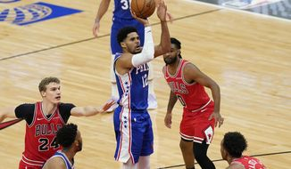 Philadelphia 76ers forward Tobias Harris (12) goes up for a shot as Chicago Bulls forward Lauri Markkanen, left, guard Coby White and center Wendell Carter Jr., right, watch during the second half of an NBA basketball game in Chicago, Thursday, March 11, 2021. (AP Photo/Nam Y. Huh)