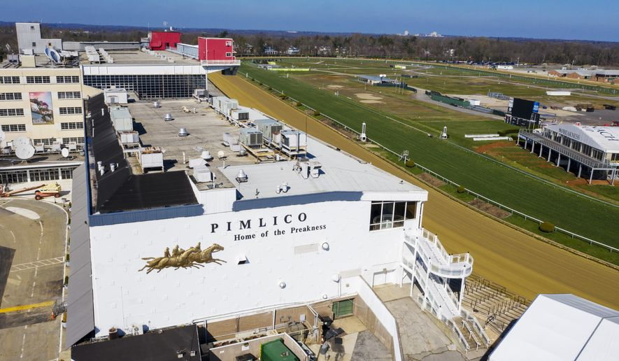 In this March 26, 2020, file photo, tractors groom the racing surface at the Pimlico Race Track in Baltimore, Md. Sports betting would be allowed online, at Maryland's six casinos and the stadiums where the state's three major professional sports teams play, as well as horse racing tracks, under a measure approved Thursday, March 11, 2021, by the House of Delegates.  (AP Photo/Steve Helber, File) **FILE**